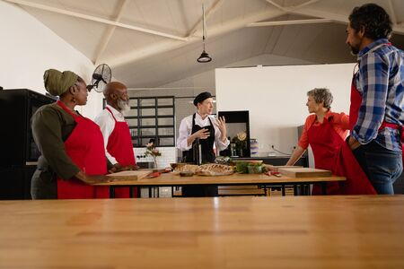 Side view of a multi-ethnic group of Senior adults at a cookery class, the diverse adult students listening to instructions from a Caucasian female chef wearing chefs whites and a black hat and apron, standing around a wooden table of ingredients wearing red aprons Reklamní fotografie