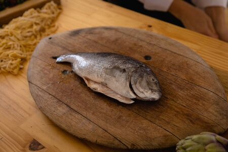High angle view of a fish on a wooden chopping board, ready for preparation, on a wooden table in a kitchen