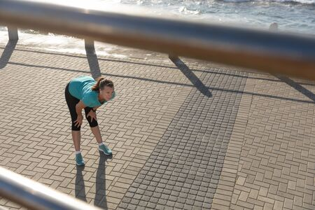 High angle side view of a mature middle aged Caucasian woman working out on a promenade on a sunny day, bending down, holding her knees, stretching