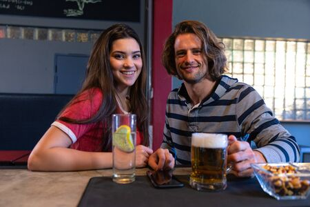 Portrait of a Caucasian woman and man sitting together at the bar in a pub during the day, looking to camera and smiling, with drinks and snacks on the bar in front of them