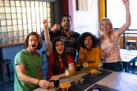 Front view of a group of five multi-ethnic male and female friends at the bar in a pub with arms in the air, cheering, having fun and celebrating while watching a sports game on TV, smiling and laughing together