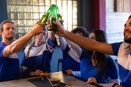 Side view close up of a group of five multi-ethnic male and female friends wearing team colours at the bar in a pub, holding bottles of beer and raising them to make a toast, smiling and laughing in celebration together while watching a sports match on TV