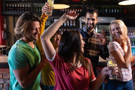 Vue de face d'un groupe de cinq amis multiethniques masculins et féminins au bar d'un pub tenant des boissons, dansant, s'amusant et célébrant, deux femmes les bras en l'air et toutes souriantes et riant ensemble Banque d'images