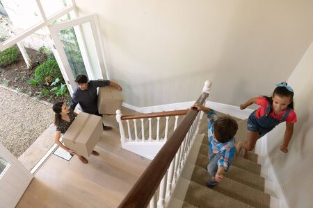 High angle view of a Caucasian couple arriving at their new home with their young son and daughter