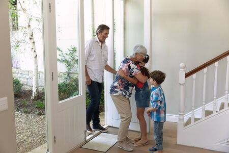 Side view of a Caucasian grandfather and grandmother arriving home and being greeted by their young grandson and granddaughter at the front door