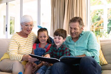 Front view of a Caucasian grand parents sitting on a sofa in the living room with their grandchildren looking at a photograph album together. Banque d'images