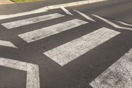Close up of empty asphalt road surface with white markings showing a pedestrian crossing point during the day