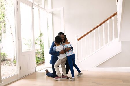 Side view of an African American man with his son and daughter at home embracing in hallway.