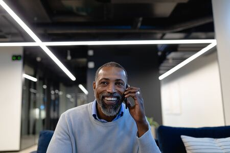 Side view of an African American businessman working in the modern office, sitting on the armchair and talking on his smartphone. Social distancing and self isolation in quarantine lockdown Stock fotó