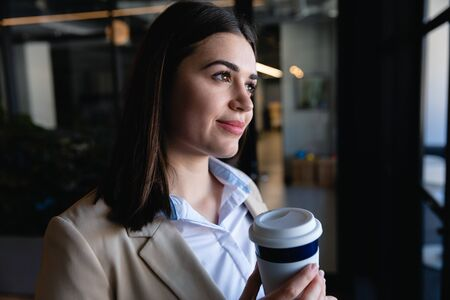 Side view close up of a Caucasian woman wearing smart clothes and earphones, working in the modern office, standing by the window and drinking coffee. Social distancing and self isolation in quarantine lockdown