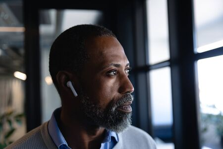 Side view close up of an African American businessman wearing earphones, working in the modern office, standing by the window and looking outside. Social distancing and self isolation in quarantine lockdown
