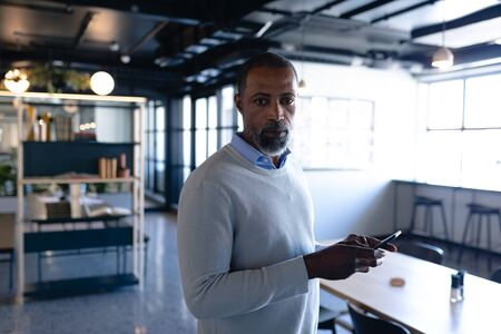 Front view of an African American businessman working in the modern office, standing by a desk, using his smartphone and looking straight into a camera. Social distancing and self isolation in quarantine lockdown Stock fotó