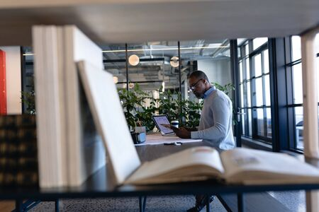 Side view of an African American businessman working in the modern office, sitting by a desk, using his laptop and using his smartphone. Social distancing and self isolation in quarantine lockdown