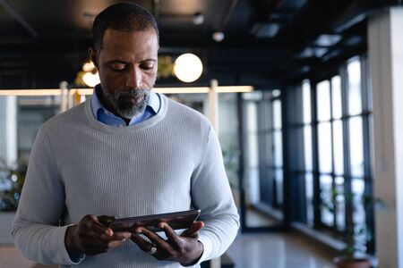 Front view of an African American businessman working in the modern office, standing by a desk and using his tablet. Social distancing and self isolation in quarantine lockdown