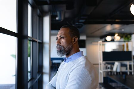 Side view of an African American businessman, working in the modern office, standing by the window and looking outside. Social distancing and self isolation in quarantine lockdown