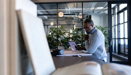 Side view of an African American businessman working in the modern office, sitting by a desk and using his smartphone. Social distancing and self isolation in quarantine lockdown Stock fotó