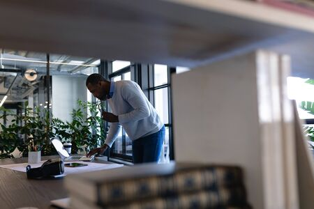 Side view of an African American businessman working in the modern office, standing by a desk, using his laptop and using his smartphone. Social distancing and self isolation in quarantine lockdown