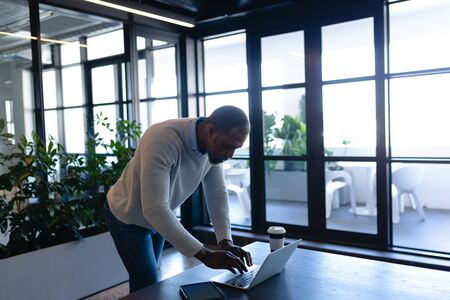 Side view of an African American businessman, working in the modern office, standing by a desk and using his laptop. Social distancing and self isolation in quarantine lockdown
