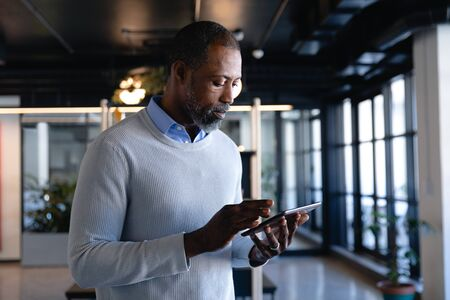 Side view of an African American businessman working in the modern office, standing by a desk and using his smartphone. Social distancing and self isolation in quarantine lockdown Stock fotó