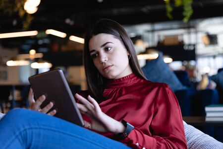Front view of a Caucasian businesswoman wearing smart clothes, working in a modern office, sitting on a bean bag and using her tablet. Social distancing and self isolation in quarantine lockdown