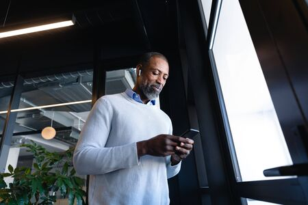 Front low angle view of an African American businessman wearing earphones, working in the modern office, smiling while using his smartphone. Social distancing and self isolation in quarantine lockdown