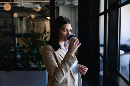 Side view of a Caucasian woman wearing smart clothes and earphones, working in the modern office, standing by the window and drinking coffee. Social distancing and self isolation in quarantine lockdown