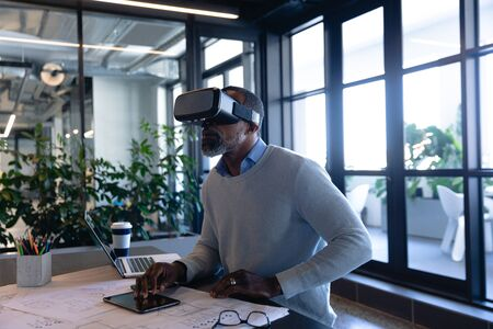 Side view of an African American businessman working in the modern office, sitting by a desk, using his tablet and VR headset. Social distancing and self isolation in quarantine lockdown