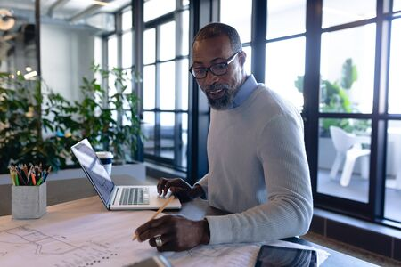 Side view of an African American businessman working in the modern office, sitting by a desk, using his laptop and drawing architectural drawing. Social distancing and self isolation in quarantine lockdown