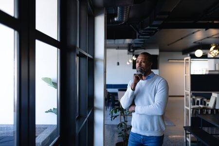 Front view of an African American businessman, working in the modern office, standing by the window, focus and thoughful. Social distancing and self isolation in quarantine lockdown Stock fotó