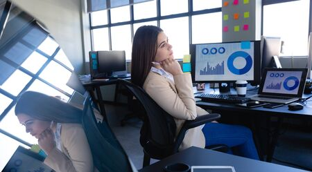Side view of a Caucasian woman working in the modern office, sitting by a desk and using her smartphone and a desktop computer and laptop showing data charts. Social distancing and self isolation in quarantine lockdown
