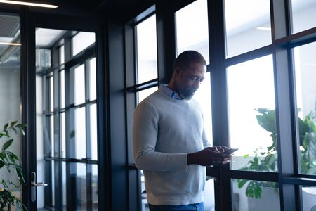 Side view of an African American businessman working in the modern office, standing by the window and talking on his smartphone. Social distancing and self isolation in quarantine lockdown Stock fotó