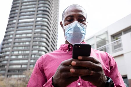 African American man out and about in the city streets during the day, wearing a face mask against air pollution and covid19 coronavirus, using his smartphone.
