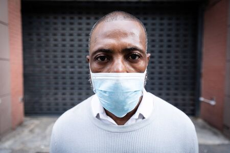 Portrait close up of an African American man out and about in the city streets during the day, wearing a face mask against air pollution and covid19 coronavirus, looking straight into a camera.