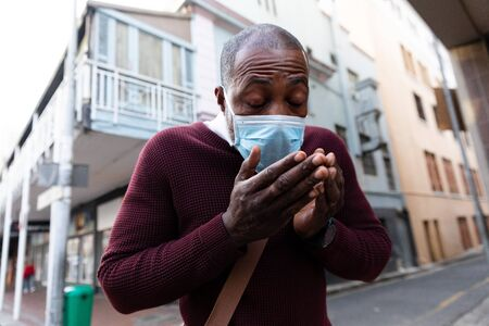 African American man out and about in the city streets during the day, wearing a face mask against air pollution and covid19 coronavirus, covering his face while coughing.