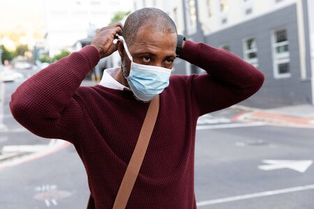 African American man wearing red pullover, out and about in the city streets during the day, putting on a face mask against air pollution and covid19 coronavirus. Stock fotó