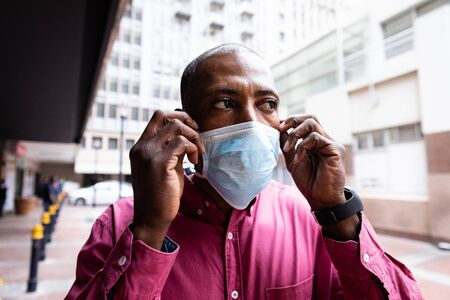 African American man out and about in the city streets during the day, putting on a face masks against air pollution and covid19 coronavirus.
