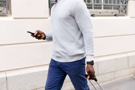 Mid section of African American man out and about in the city streets during the day, pulling a suitcase and using his smartphone.