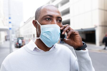 African American man out and about in the city streets during the day, wearing a face mask against air pollution and covid19 coronavirus, talking on his smartphone.