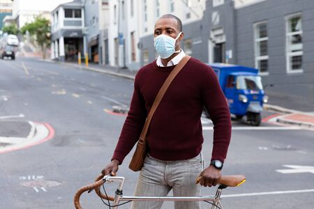 African American man out and about in the city streets during the day, wearing a face mask against air pollution and covid19 coronavirus, wheeling his bicycle.