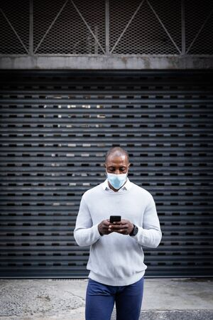 African American man out and about in the city streets during the day, wearing a face mask against air pollution and covid19 coronavirus, standing in front of a gate and using his smartphone. Stock fotó