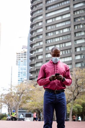 African American man out and about in the city streets during the day, wearing a face masks against air pollution and covid19 coronavirus, using his smartphone.