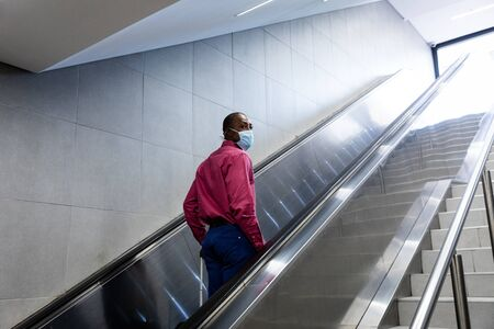 African American man wearing a face masks against air pollution and covid19 coronavirus, standing on escalator.
