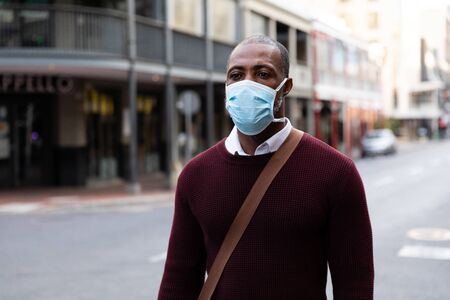 African American man out and about in the city streets during the day, wearing a face mask against air pollution and covid19 coronavirus, walking.