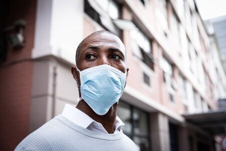 African American man out and about in the city streets during the day, wearing a face masks against air pollution and covid19 coronavirus.