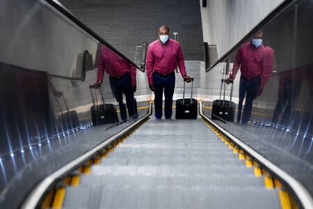 African American man wearing a face masks against air pollution and covid19 coronavirus, standing on escalator and holding a suitcase.