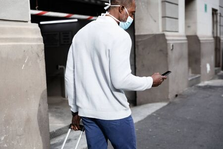 African American man out and about in the city streets during the day, wearing a face mask against air pollution and covid19 coronavirus, pulling a suitcase and using his smartphone. Stock fotó