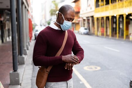African American man out and about in the city streets during the day, wearing a face mask against air pollution and covid19 coronavirus, using his smartwatch. Stock fotó