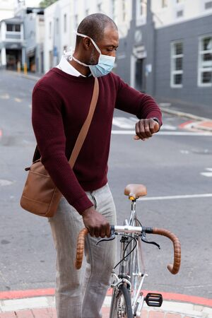 African American man out and about in the city streets during the day, wearing a face mask against air pollution and covid19 coronavirus, wheeling his bicycle and using his smartwatch. Stock fotó
