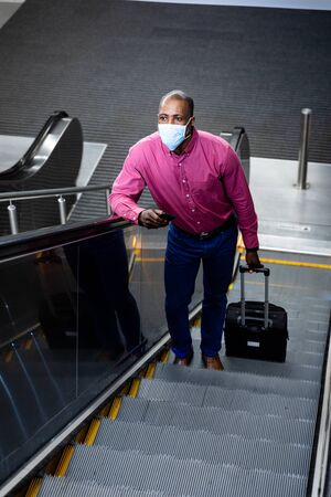 African American man wearing a face masks against air pollution and covid19 coronavirus, standing on escalator, using his smartphone and holding a suitcase.