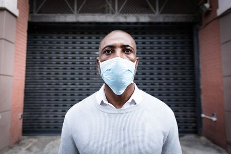 African American man out and about in the city streets during the day, wearing a face mask against air pollution and covid19 coronavirus, standing in front of a gate. Stock fotó